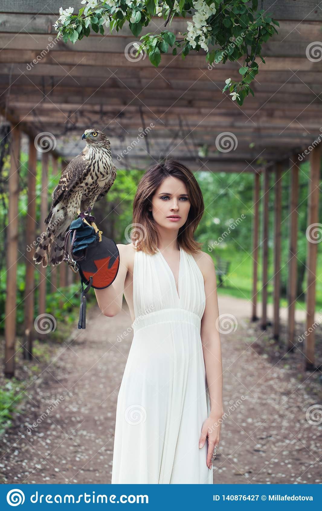Young woman in white dress holding hawk bird outdoor