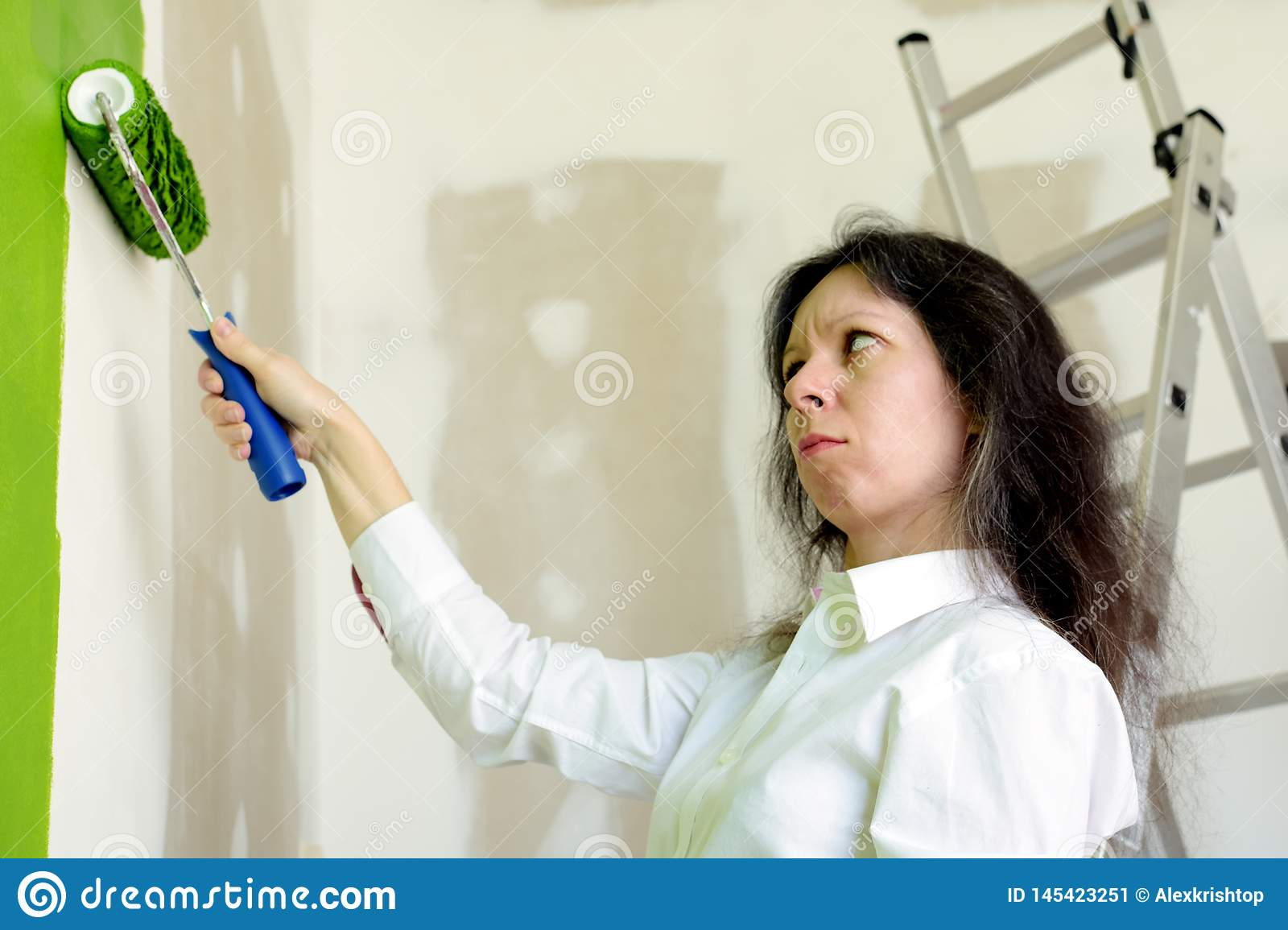 Young woman in white shirt upset with a green color of a painted wall