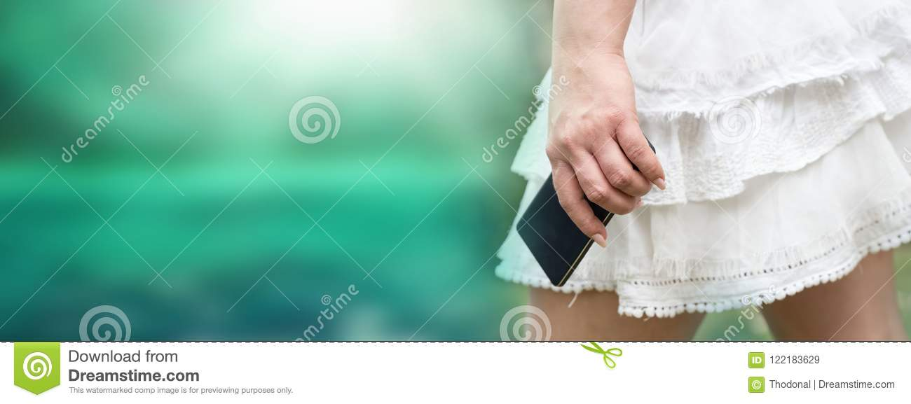 Young woman in white skirt with mobile phone in her hand