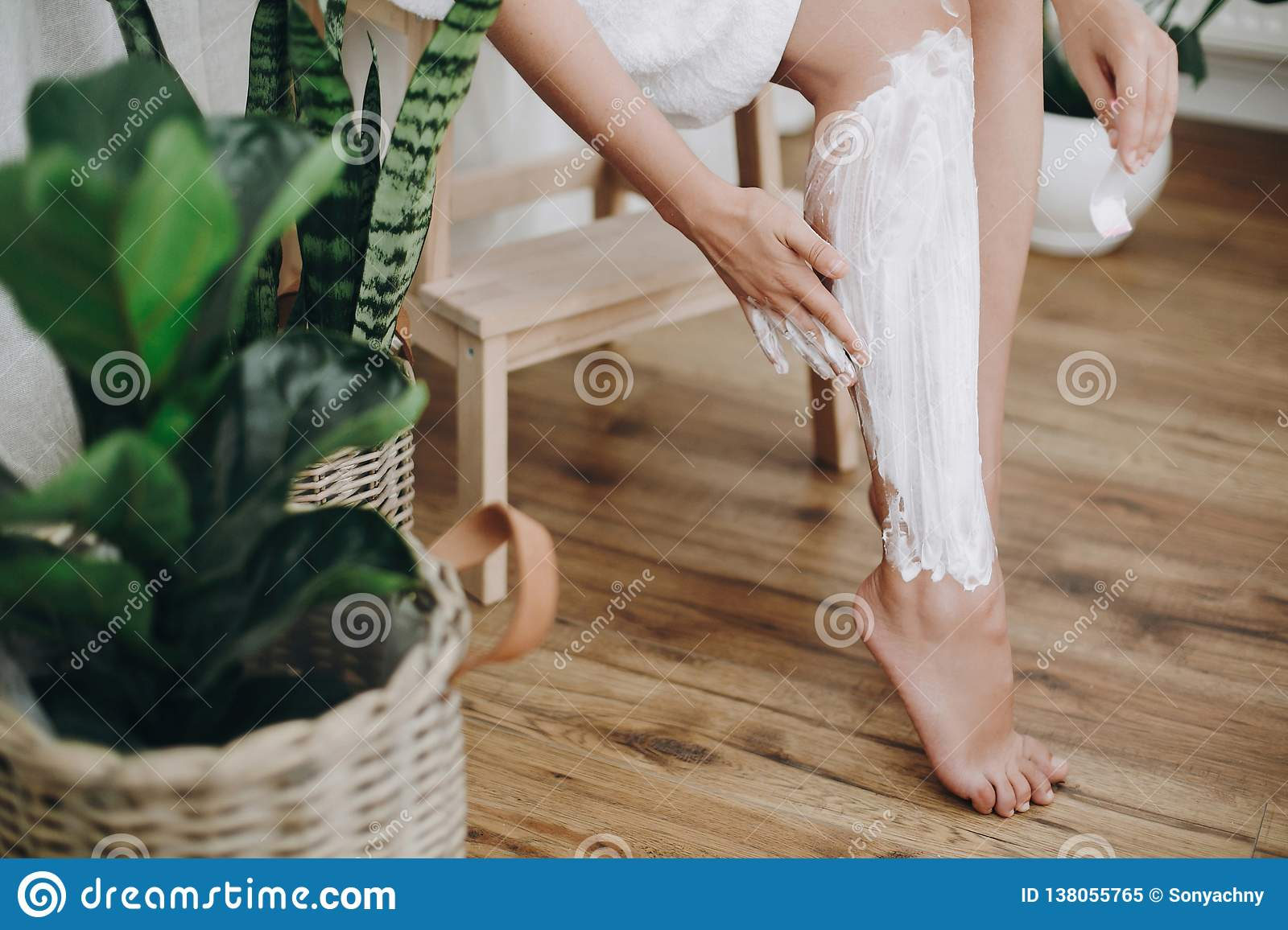 Young woman in white towel applying shaving cream on her legs in home bathroom with green plants. Skin care and wellness concept.