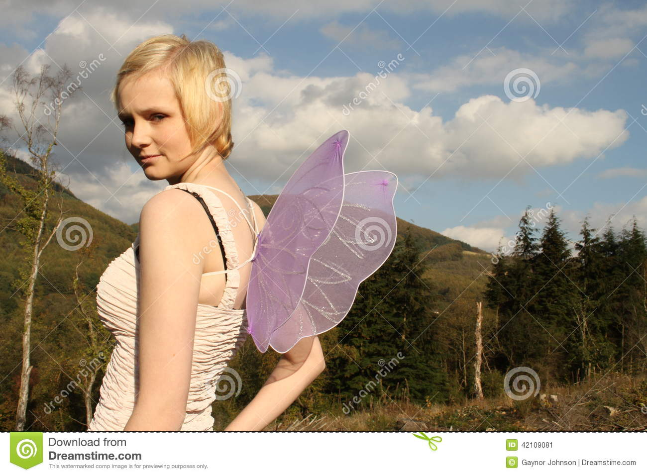 Young woman with wings against bright blue sky