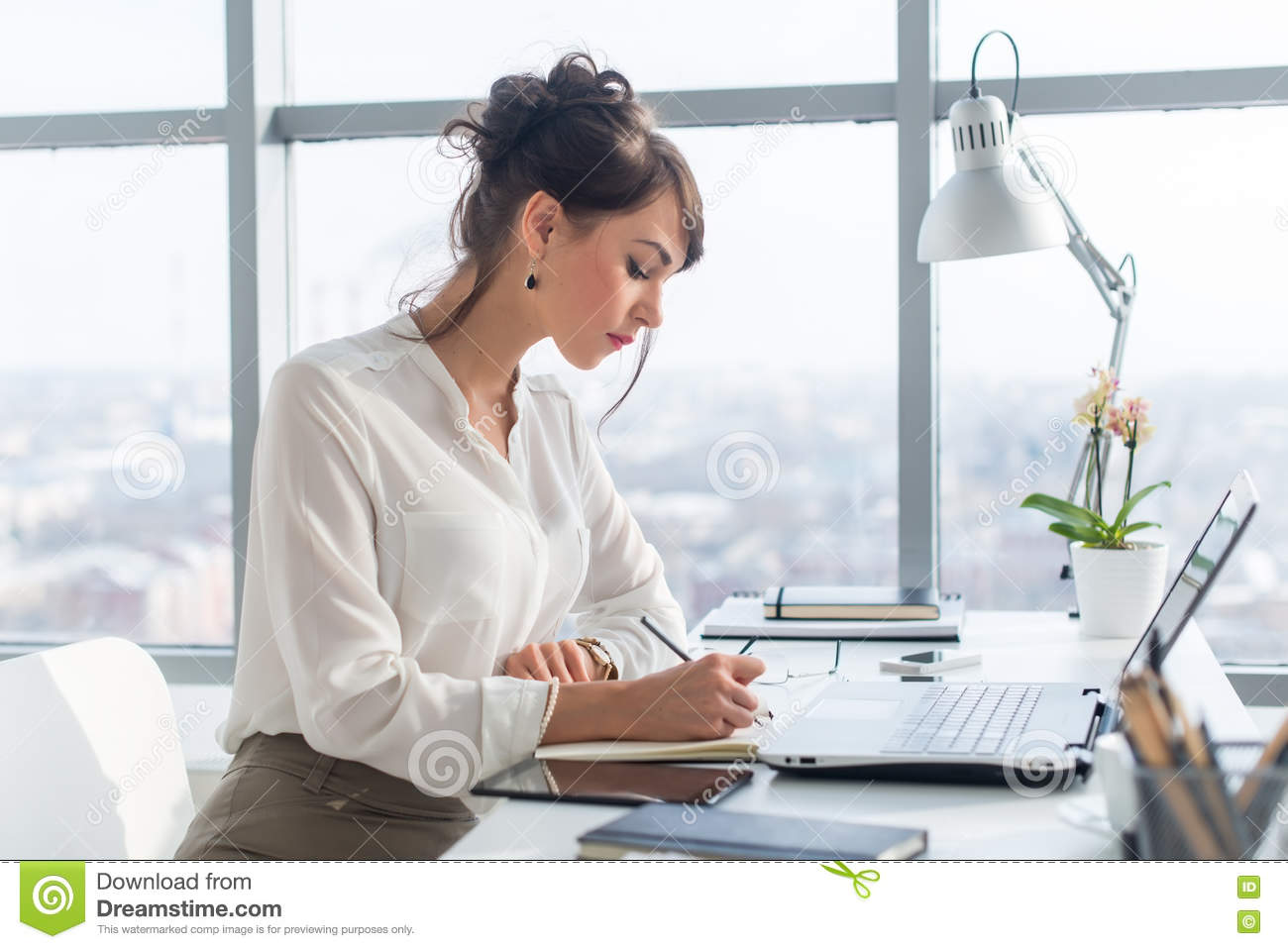 Young woman working as an office manager, planning work tasks, writing down her schedule to planner at the workplace.