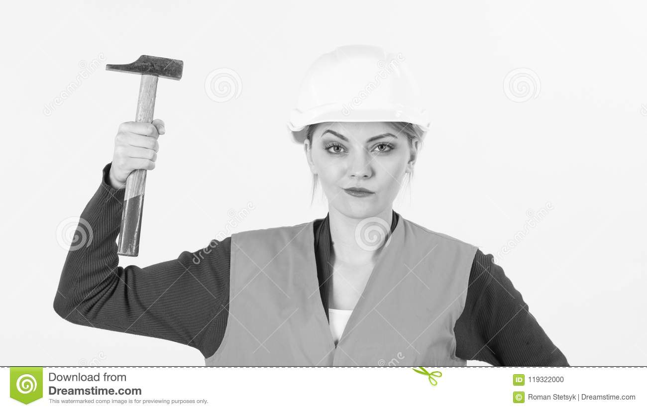 619fa5965a64f Young woman works as builder. Strong and independent concept. Girl in  helmet or hard hat raise up hammer. Woman with cunning face holds hammer