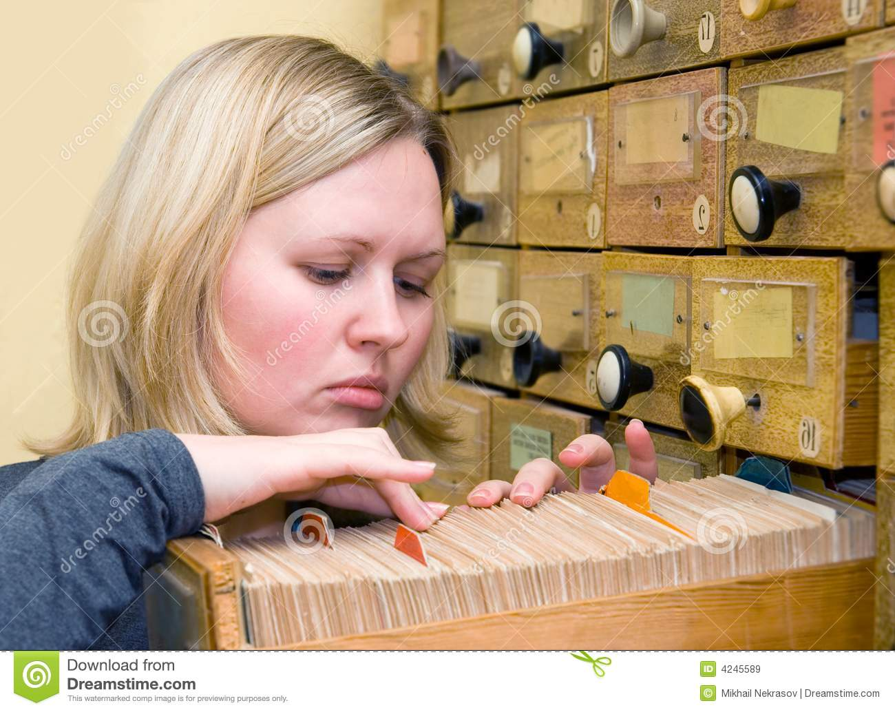 Young woman works with library card index
