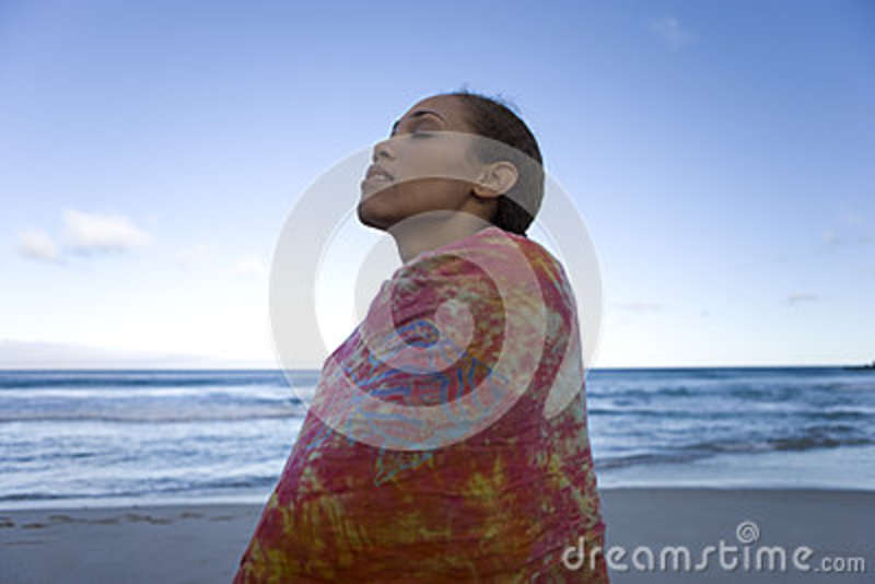 Young woman wrapped in sarong on beach, eyes closed, low angle view