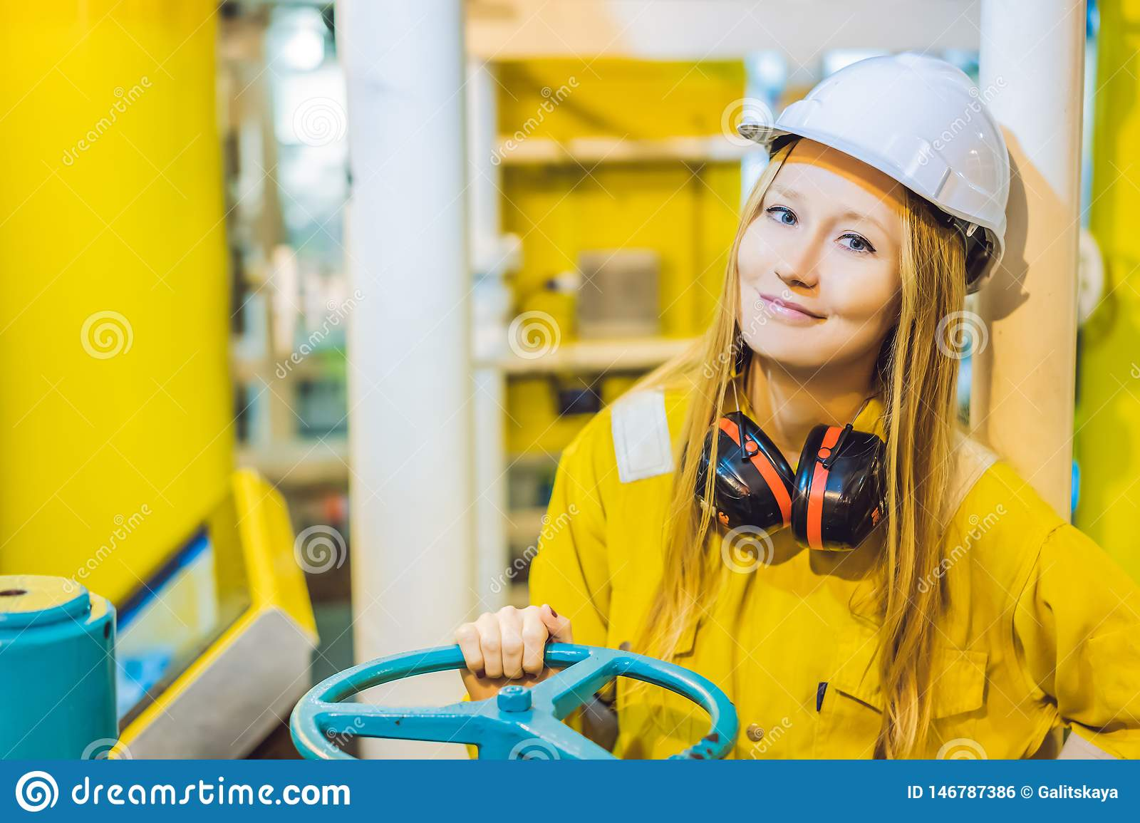 Young woman in a yellow work uniform, glasses and helmet in industrial environment,oil Platform or liquefied gas plant