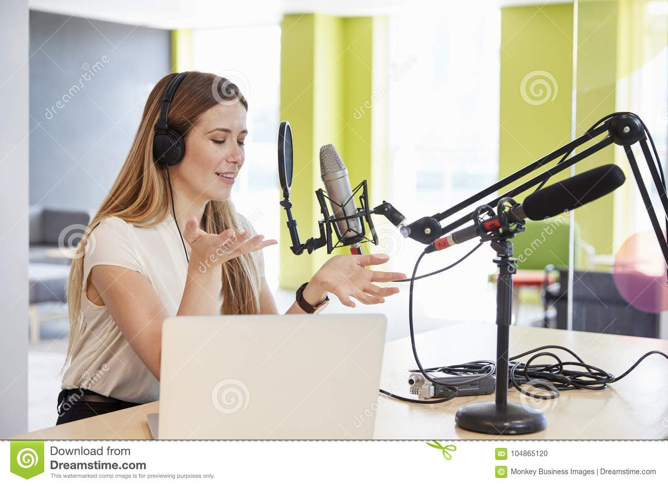 Young woman broadcasting in a studio gesturing, close up