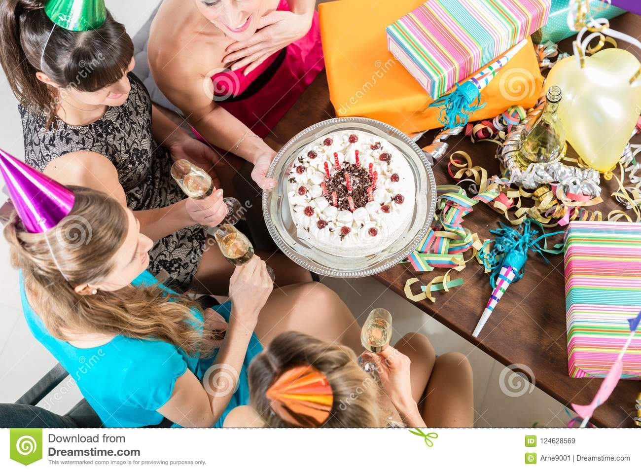 Young women celebrating with cake and champagne a birthday