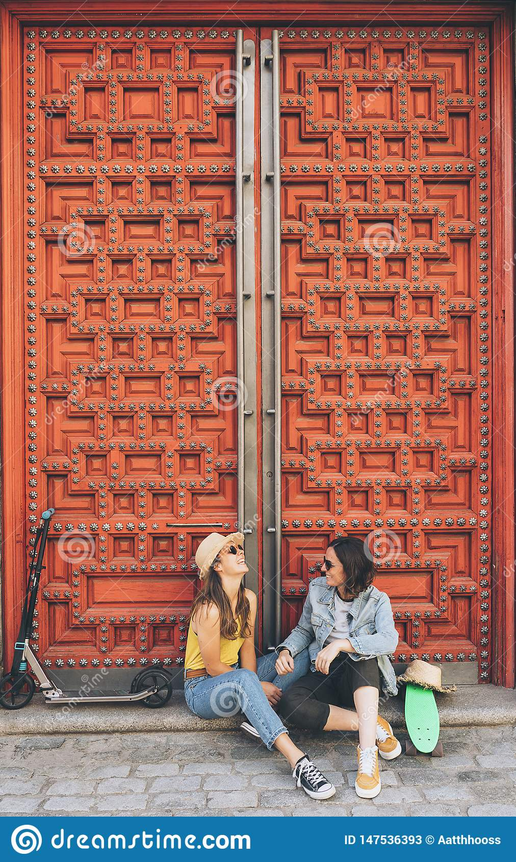 Young women gay couple looking and smiling each other in a red door background. Same sex happiness and joyful concept