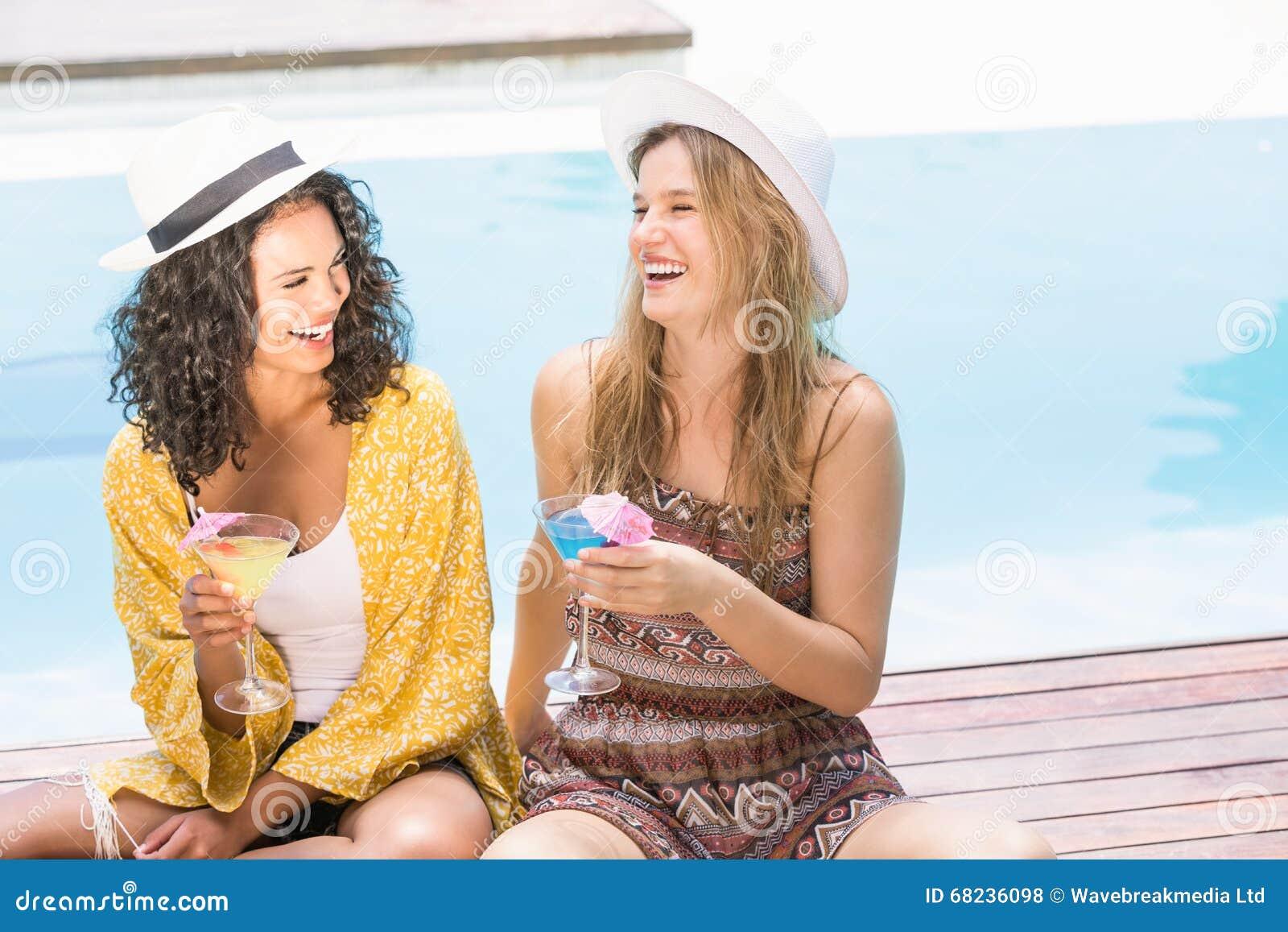 Young women having martini near pool