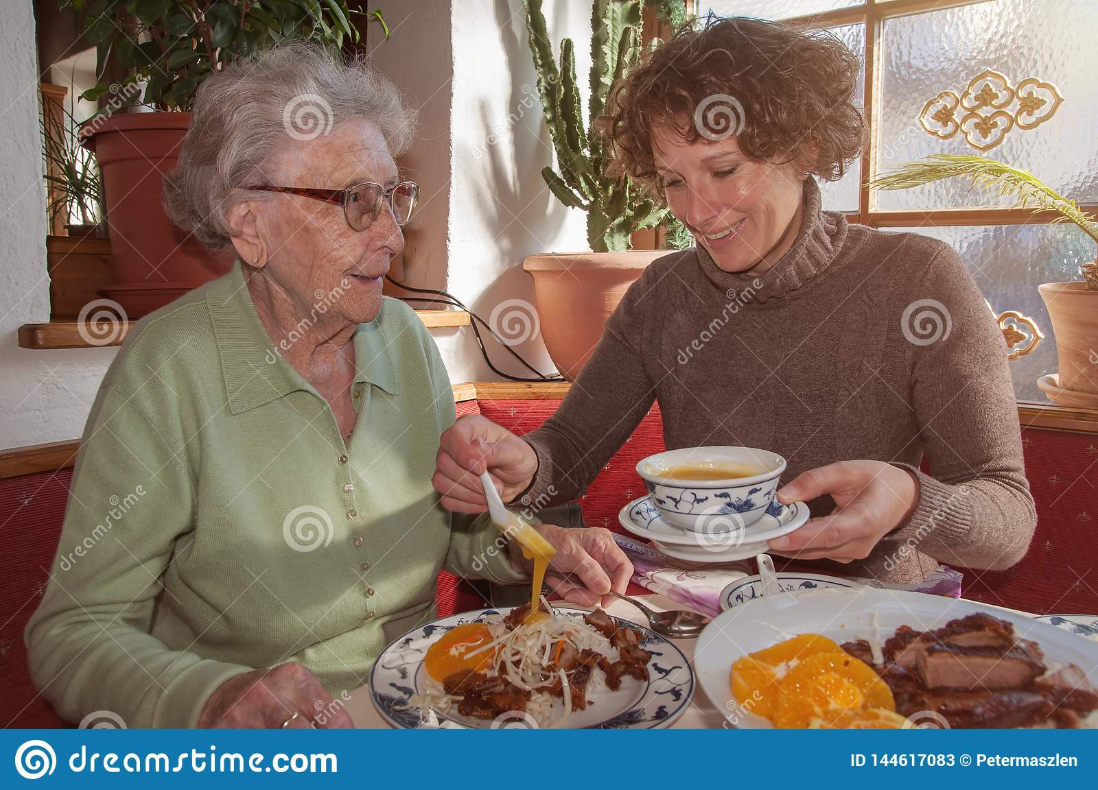 Young woman and her happy grandmother having lunch at restaurant