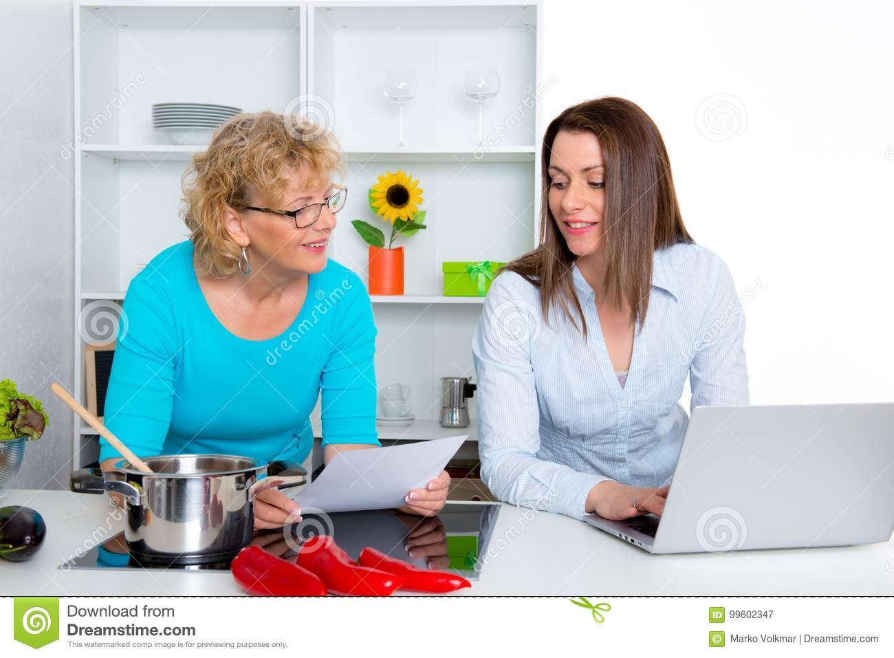 Young Woman And Her Mother Together In The Kitchen And Using Lap ...