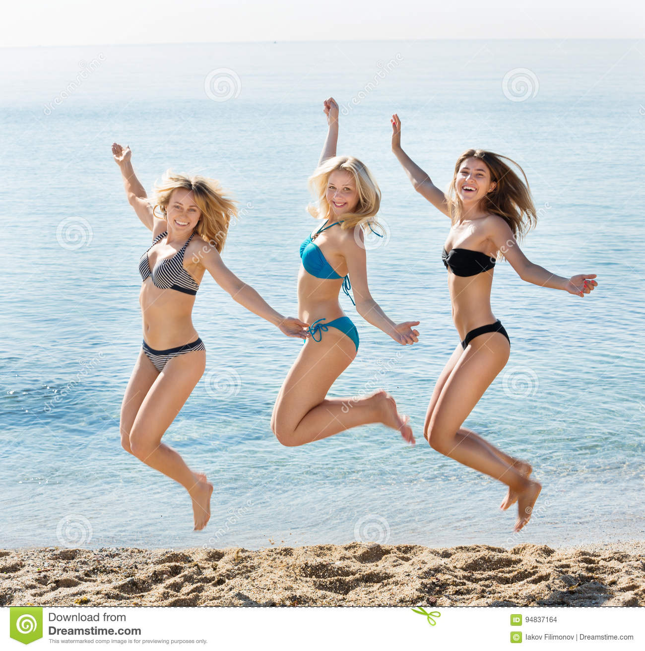 Young women hopping on beach