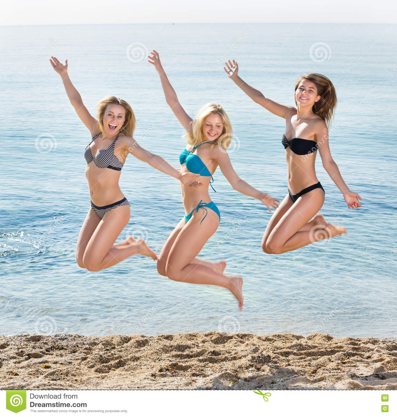 8d0cd00564c4b Portrait of three cheerful young women in swimsuits hopping together on  beach. Focus on left person