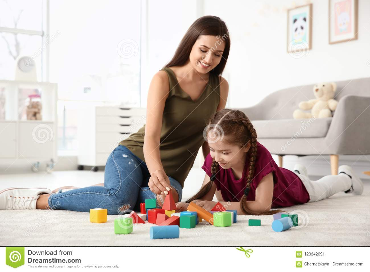 Young woman and little girl with autistic disorder playing