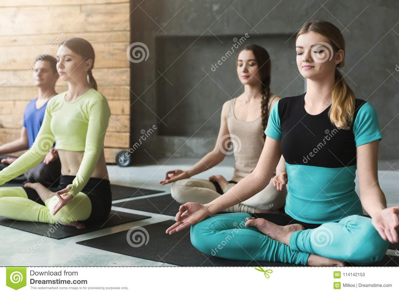 Young Women And Men In Yoga Class Relax Meditation Pose Stock Image