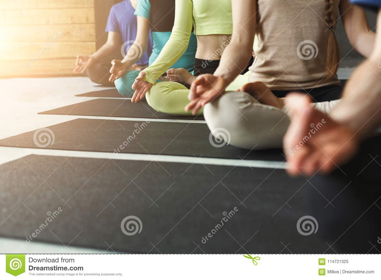 Young women and men in yoga class, relax meditation pose