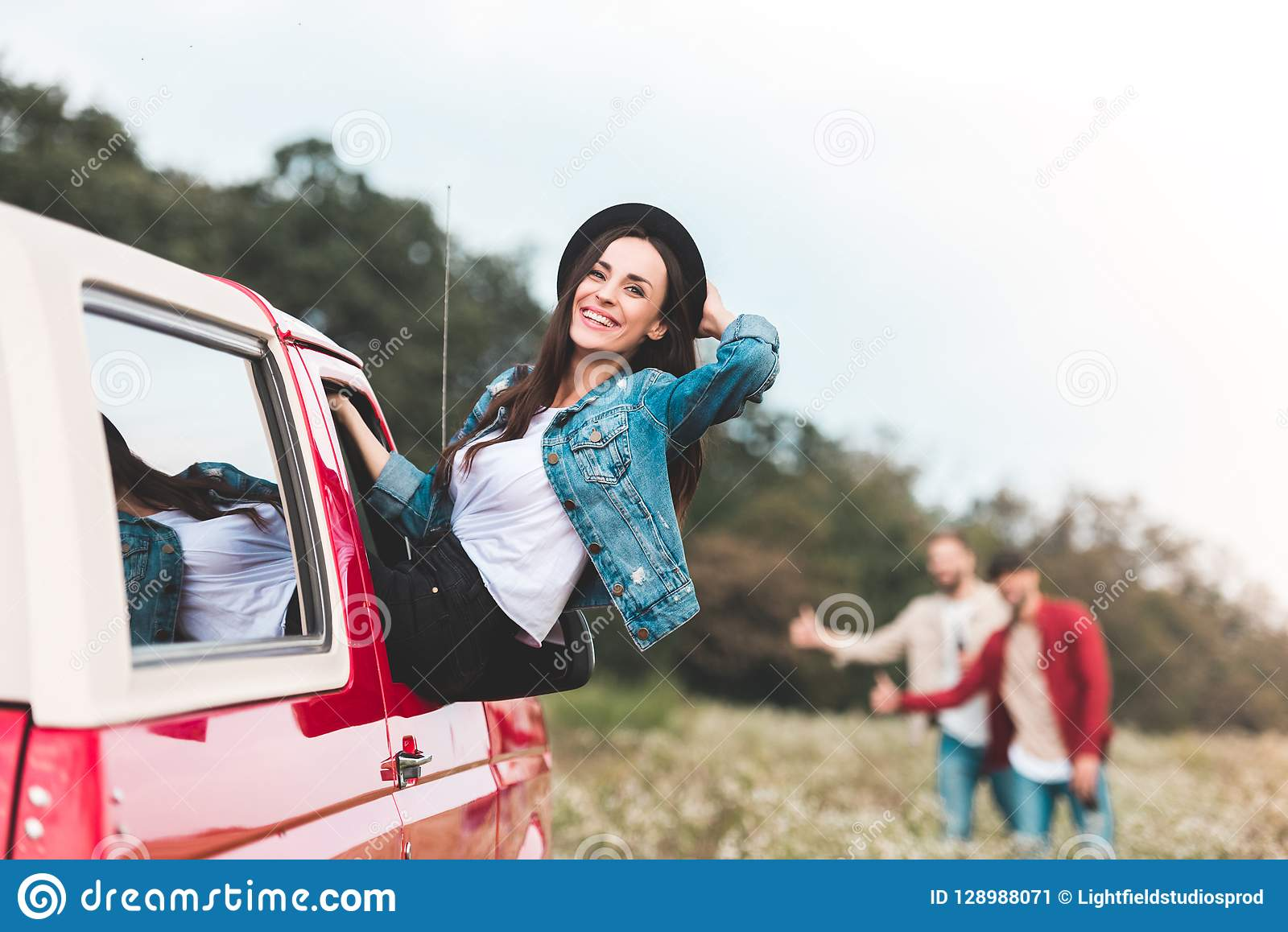 young woman outstretching from car window while men hitchhiking blurred