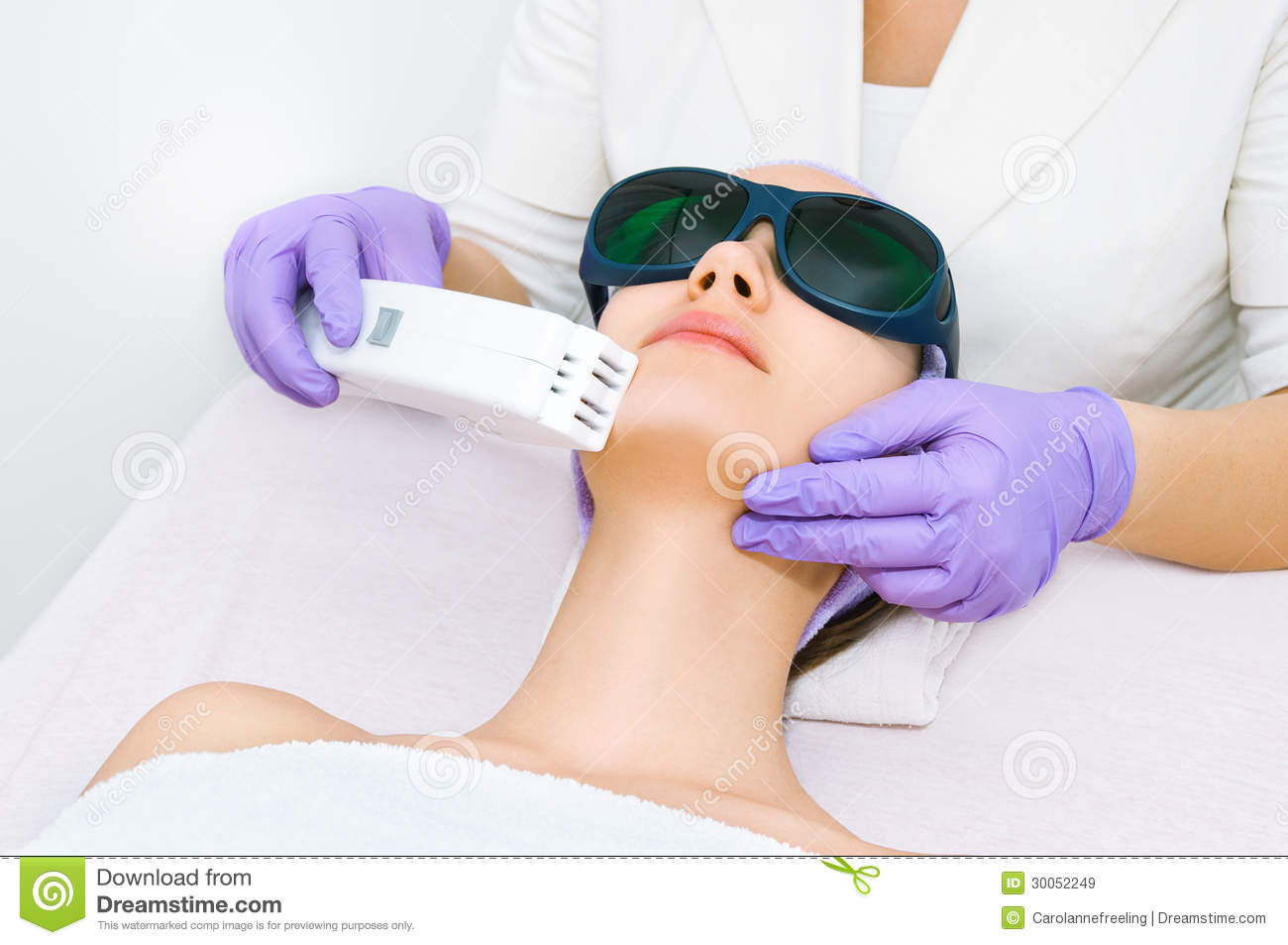 young woman receiving epilation laser treatment stock