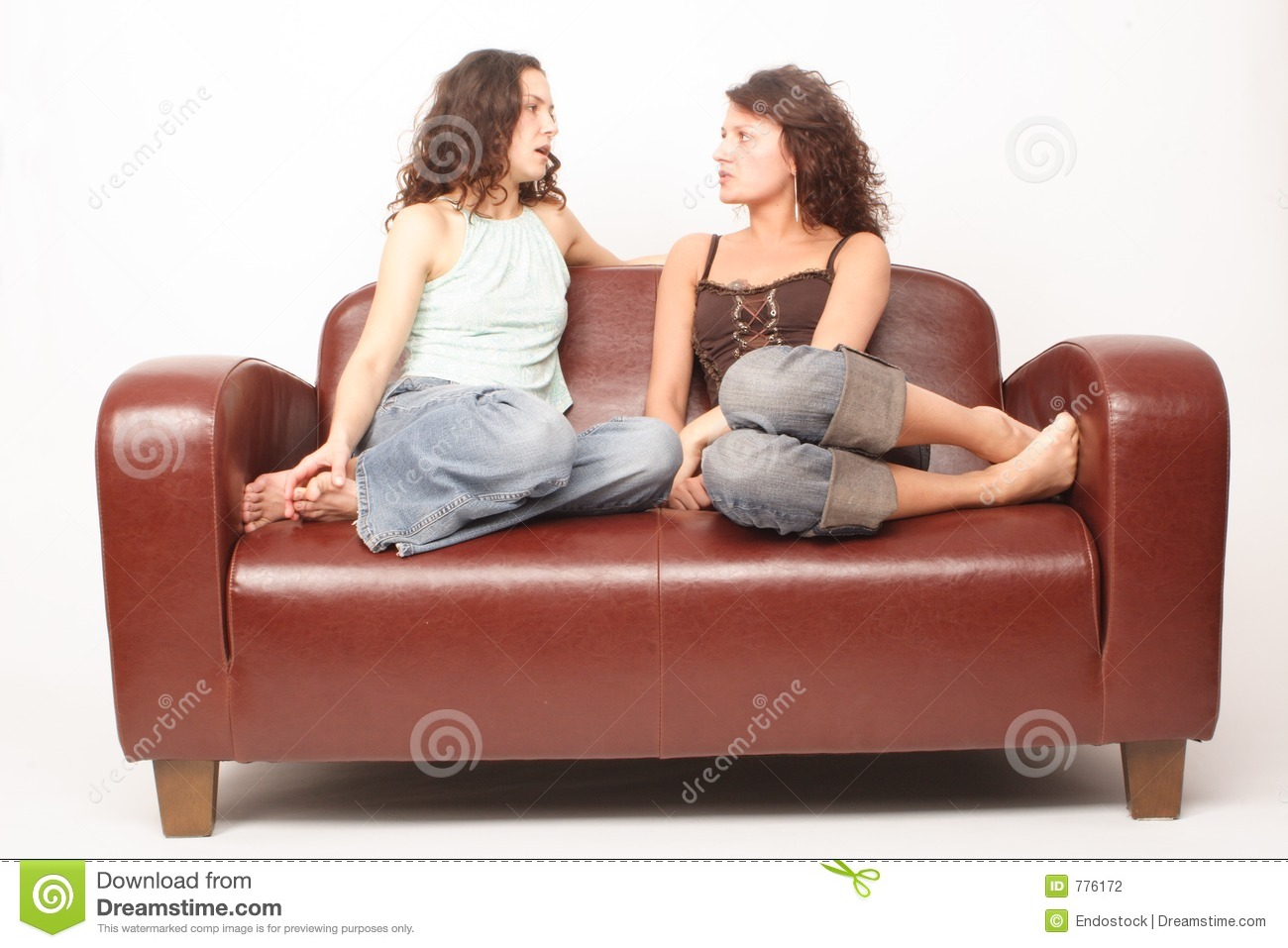 Young women sitting on sofa and talking