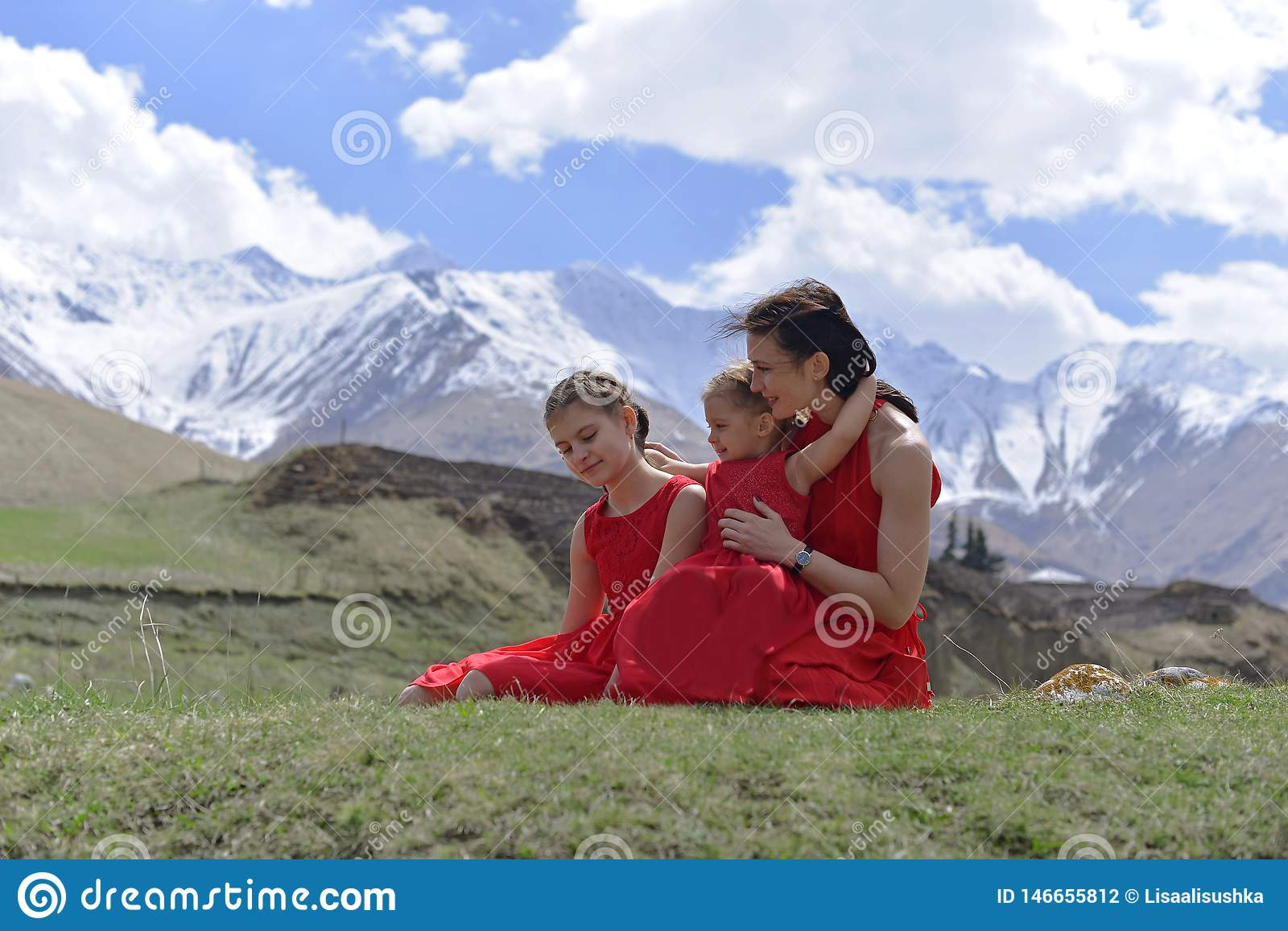 A young woman with two daughters in red dresses resting in the snow-capped mountains in the spring.