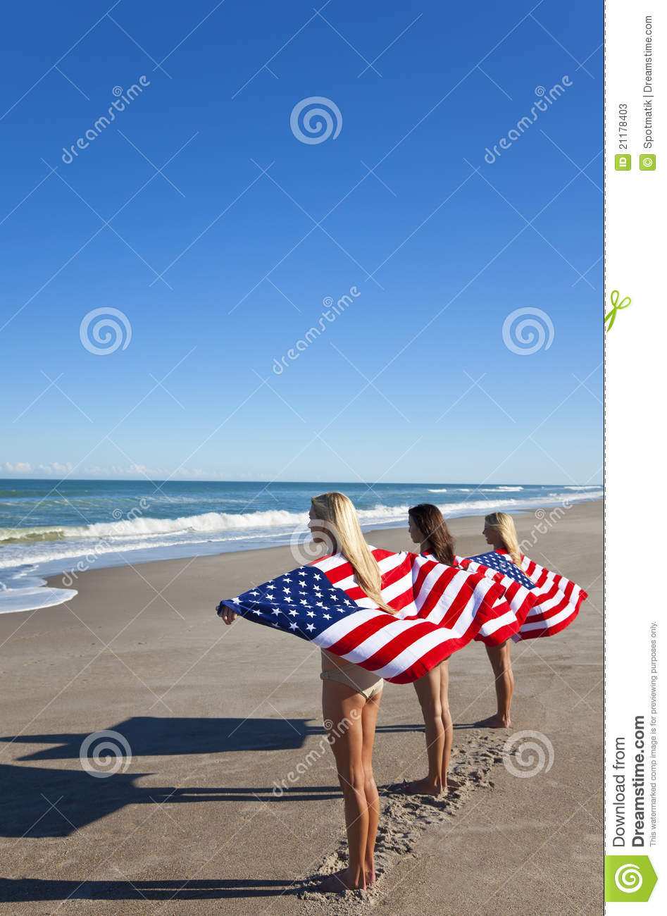 Young Women Wrapped in American Flags on a Beach