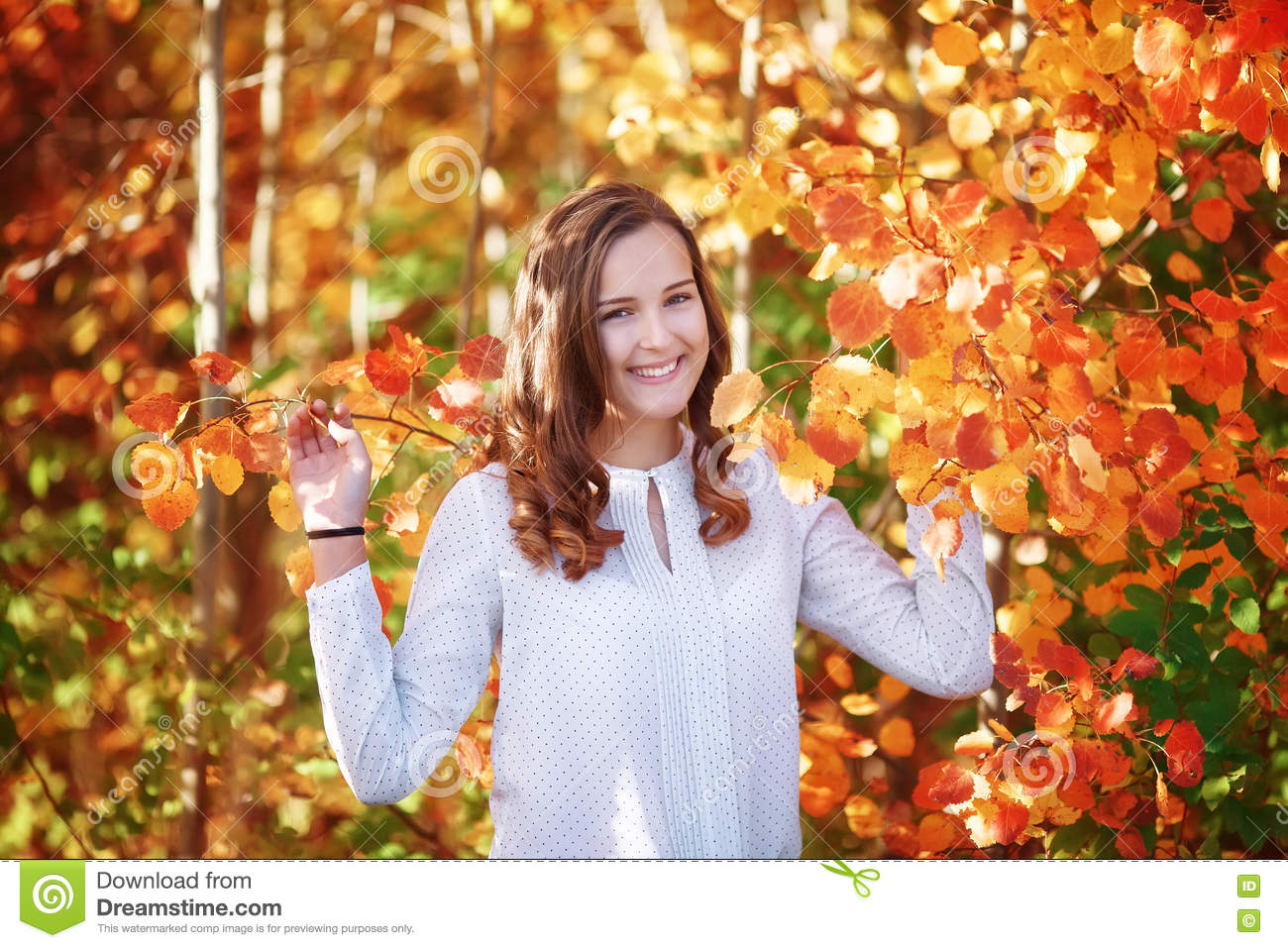 Young wooman. Pretty smiling girl in bright autumn orange leaves
