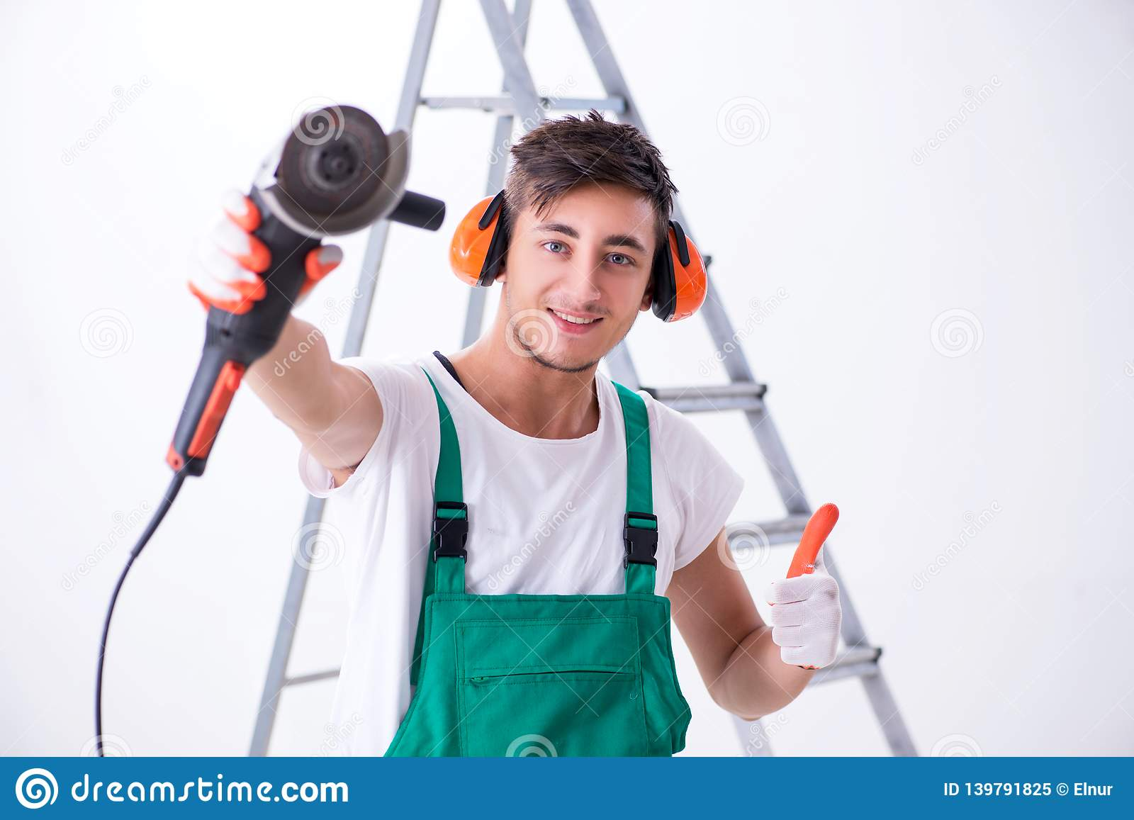 The young worker with earmuffs in noise cancelling concept