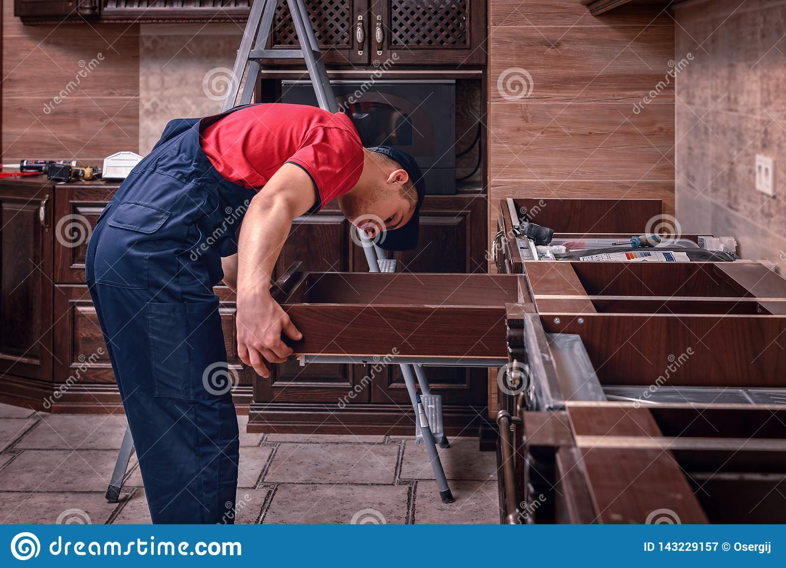 A young worker installs a drawer. Installation of modern wooden kitchen furniture