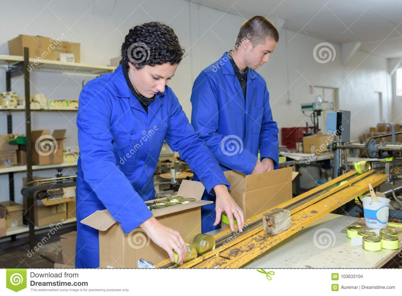 Young workers packing products off factory production line
