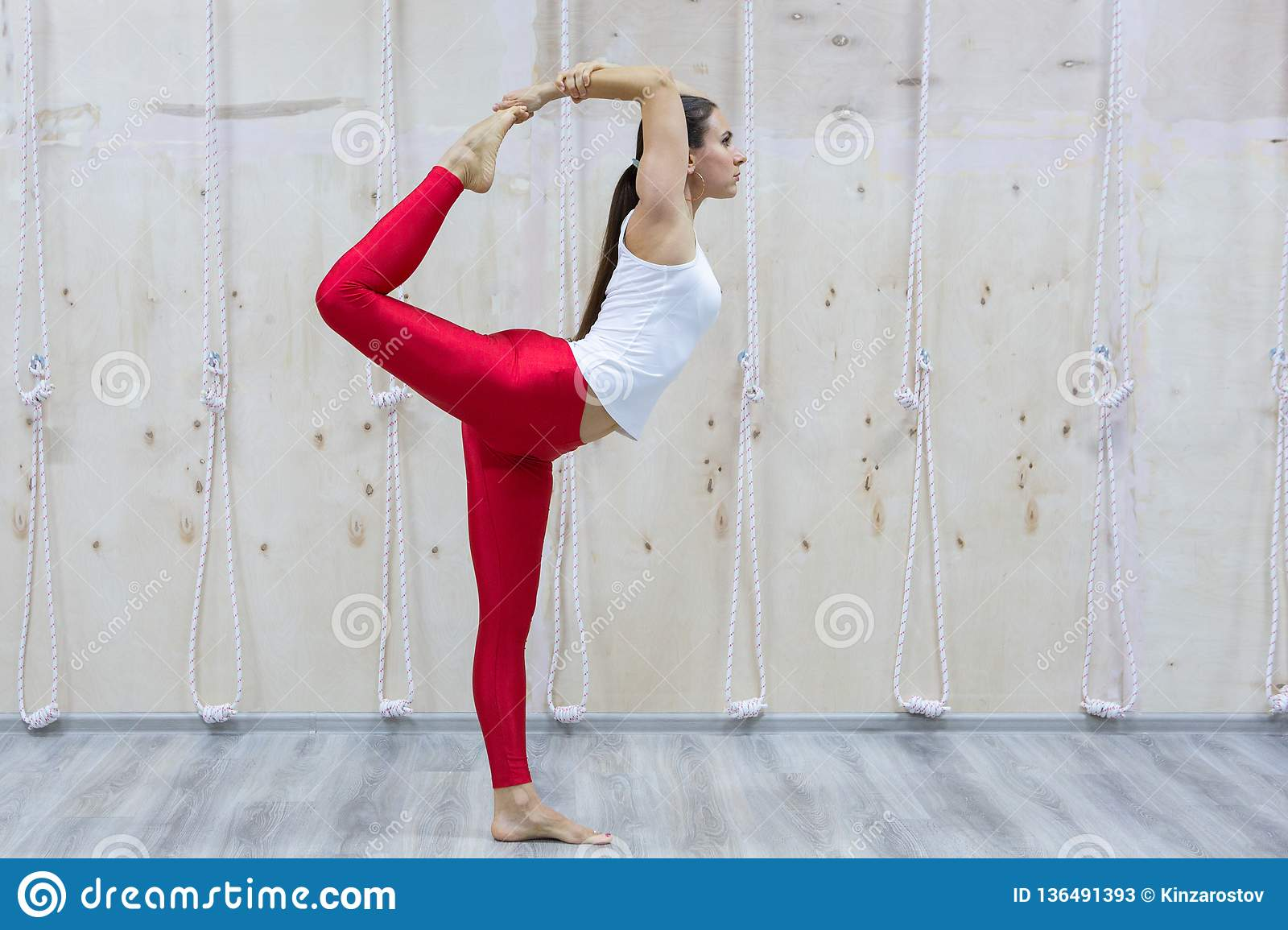 Young yogi attractive woman practicing yoga concept, standing in Natarajasana exercise
