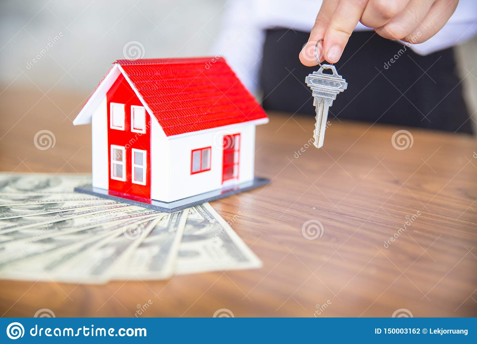 Your new house, woman hands holding a model house and key. Mortgage property insurance dream moving home and real estate concept