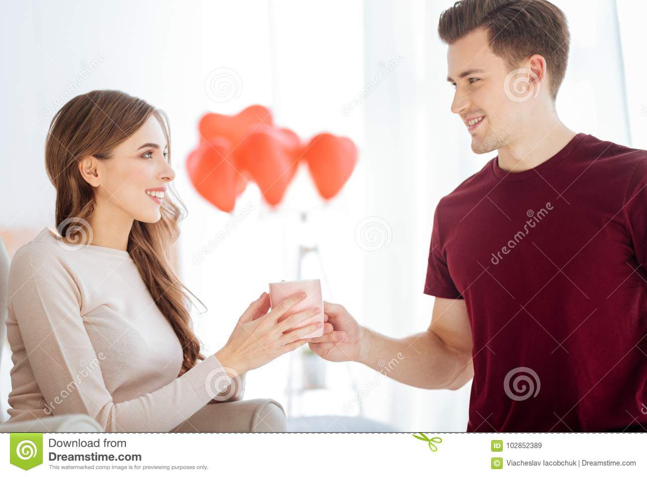 Mindful Guy Bringing Cup Of Tea For Girlfriend Stock Image