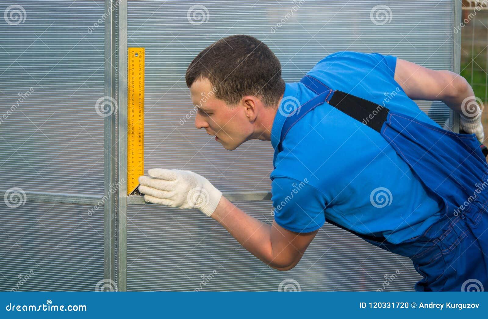 Yrkesmässig arbetare, kontroller med hjälpen av en fyrkant riktigheten av installationen av växthuset, polycarbonate