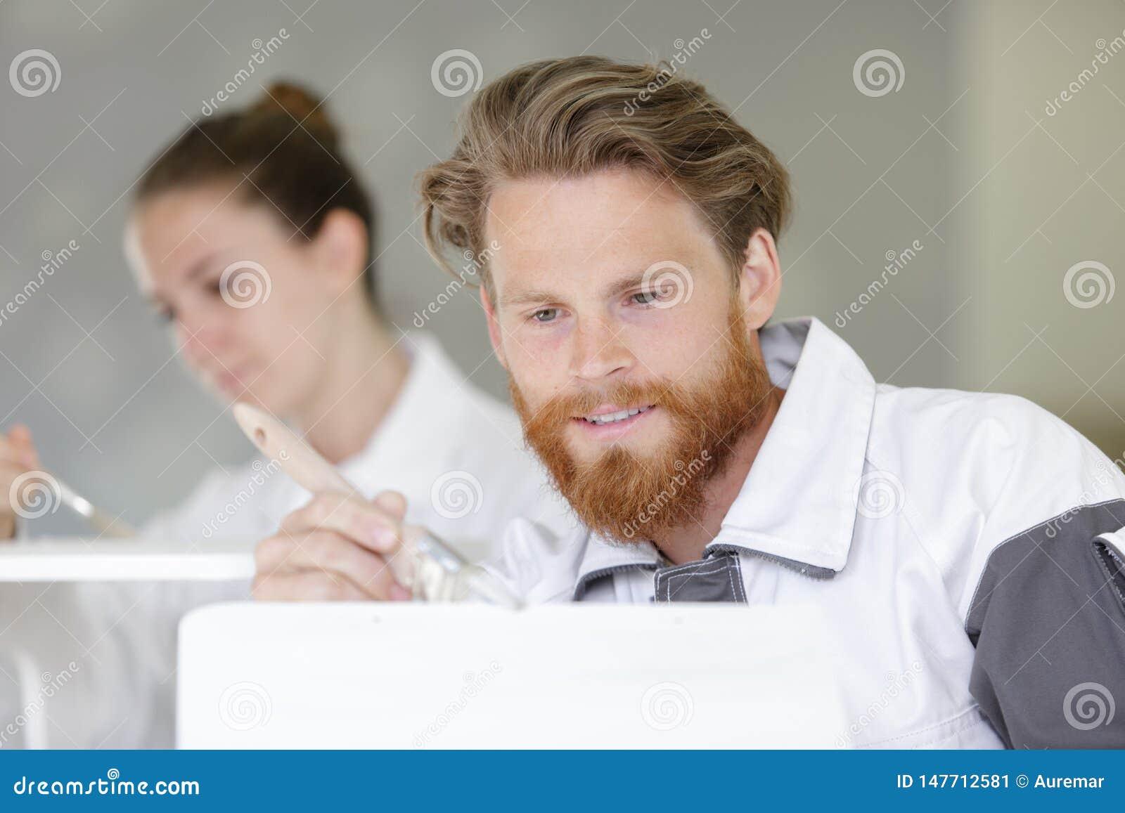 Yrkesmässig arbetare som målar försiktigt objekt med vit målarfärg