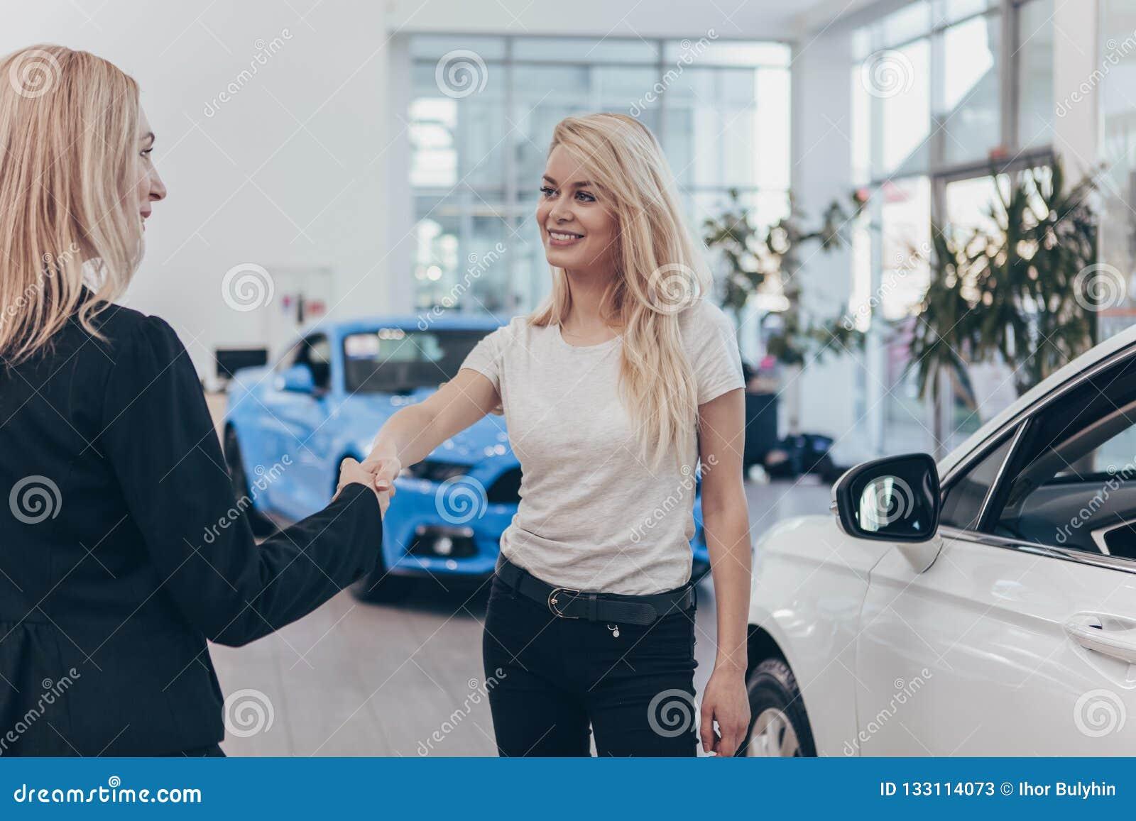 Yrkesmässig bilåterförsäljare som hjälper hennes kvinnliga kund