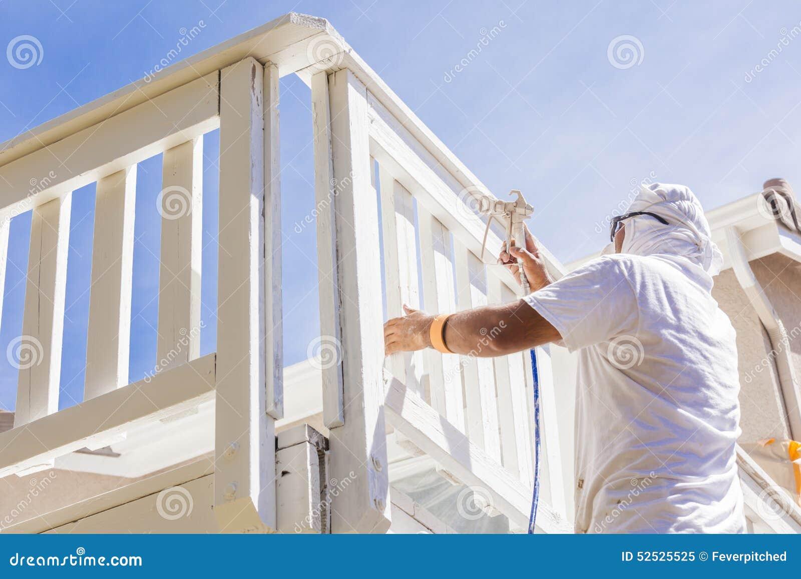 Yrkesmässig husmålare Spray Painting ett däck av ett hem