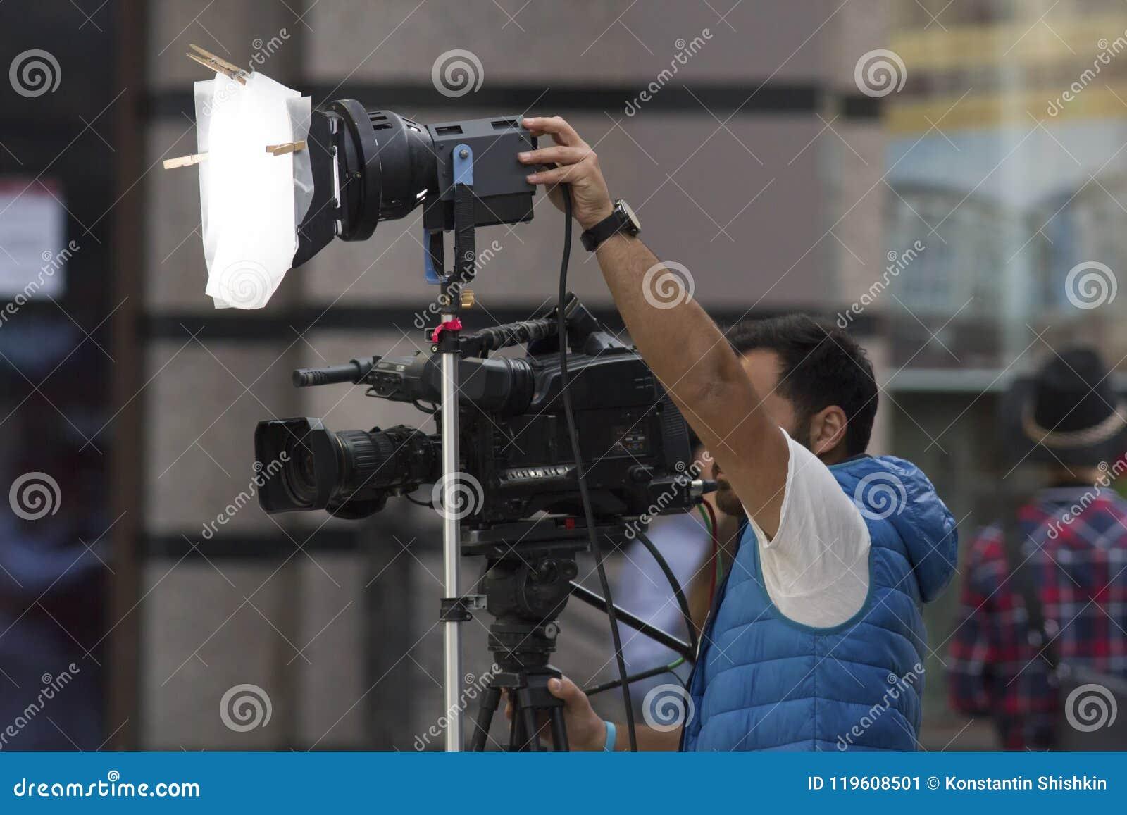 Yrkesmässig kameraman som skjuter en video på gatan