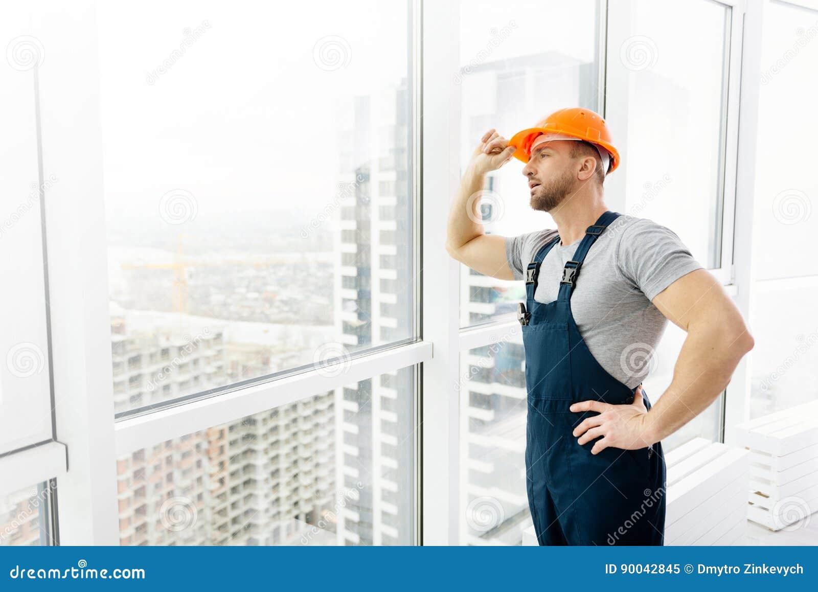 Yrkesmässig konstruktionstekniker som står det near fönstret