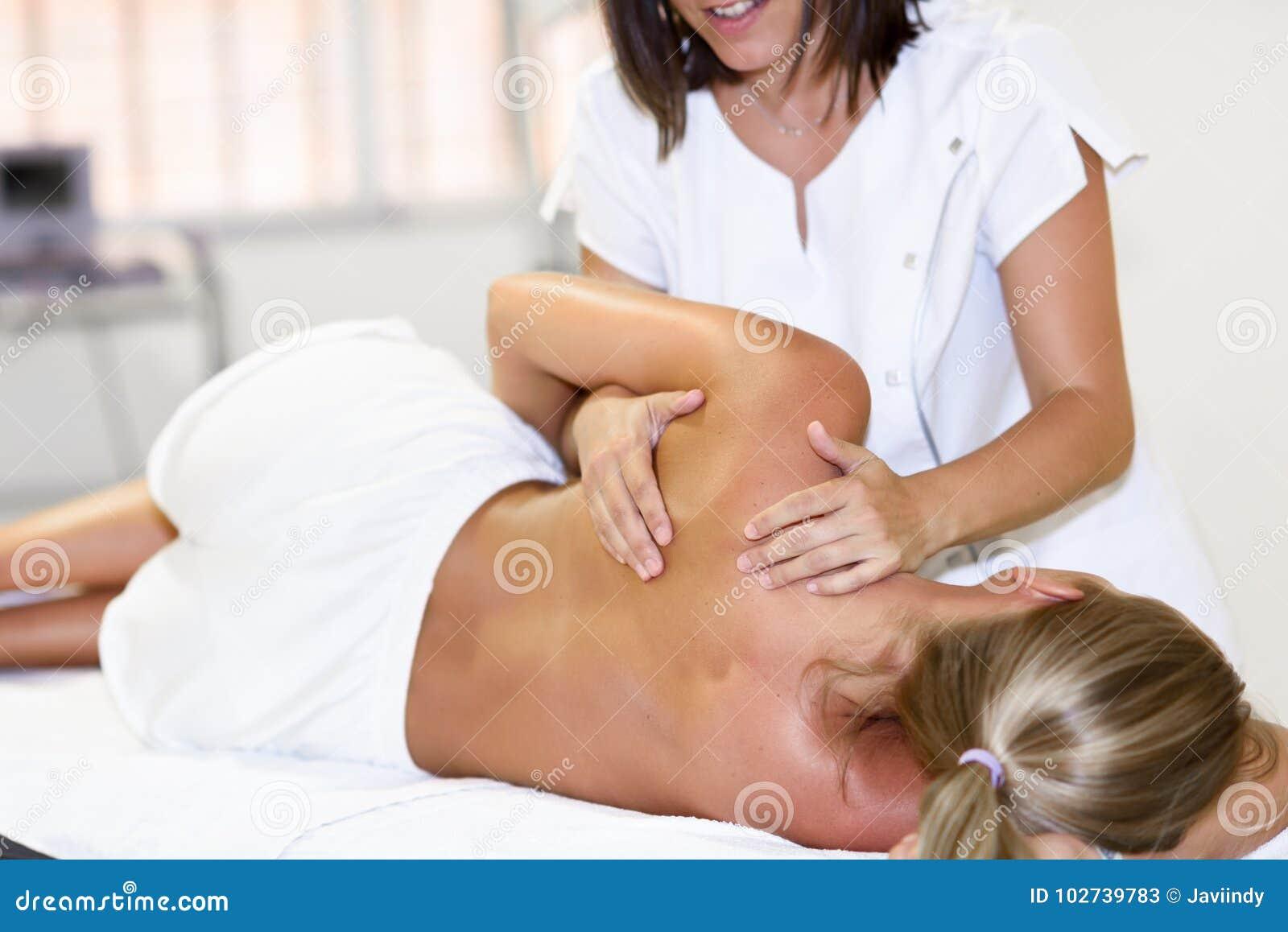 Yrkesmässig kvinnlig fysioterapeut som ger skuldramassage till b