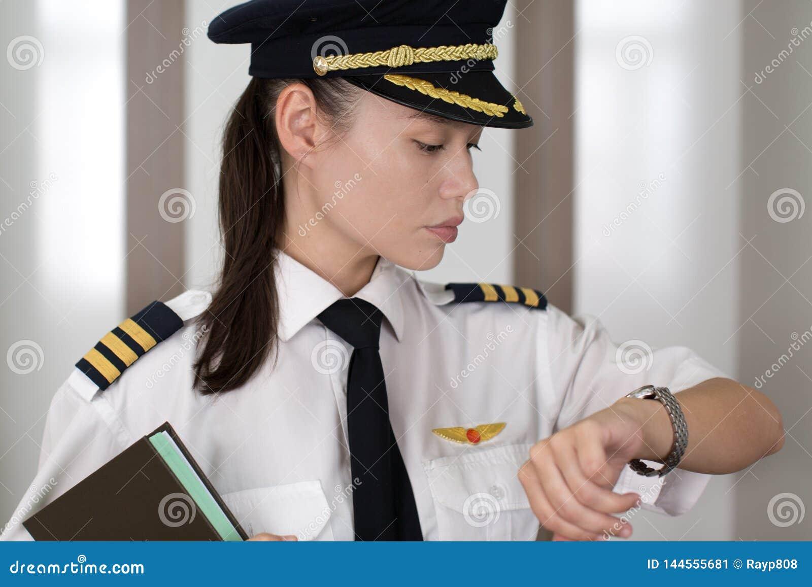 Yrkesmässig kvinnlig pilot som kontrollerar tiden på honom flygplats
