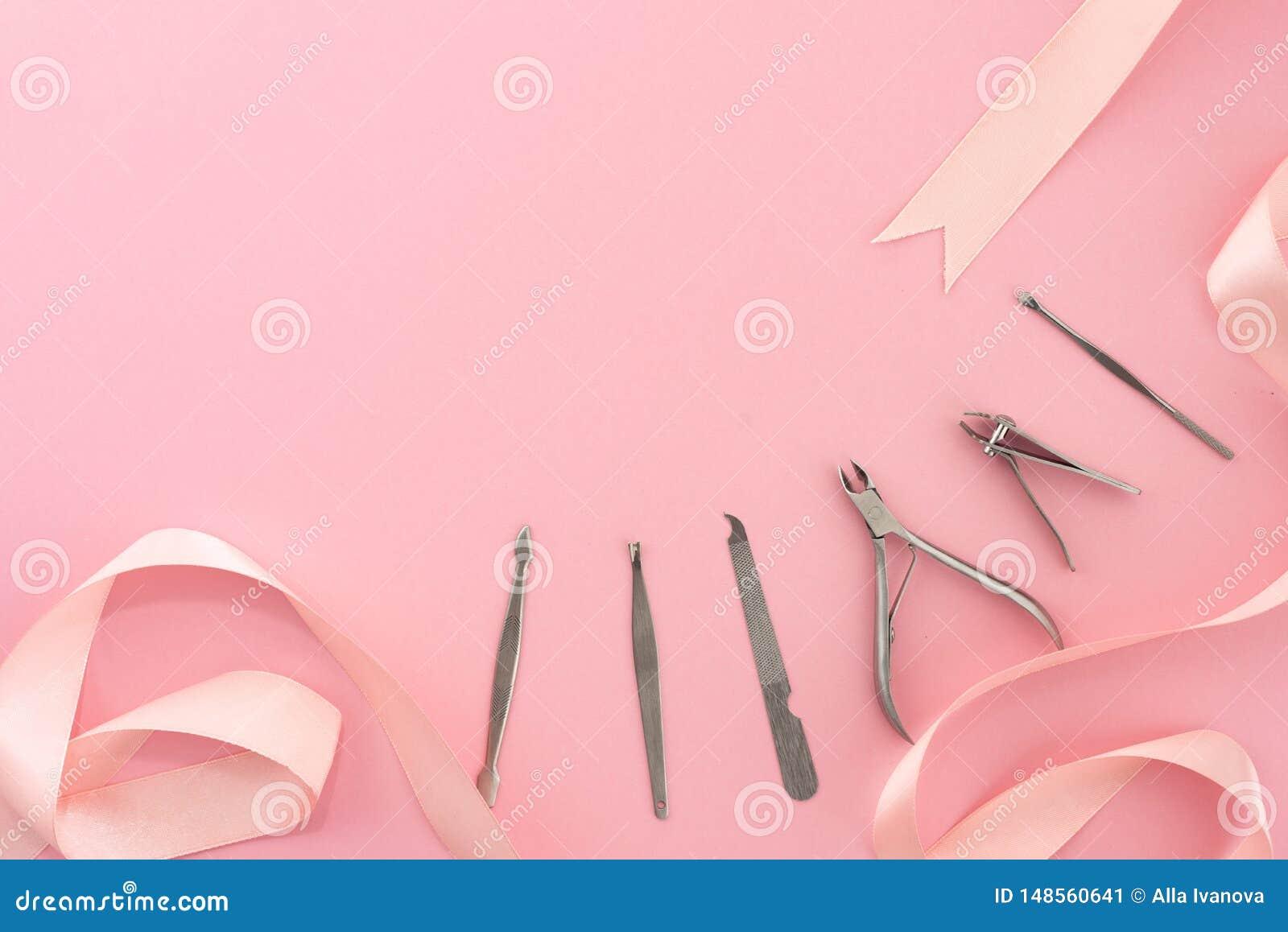 Yrkesmässiga hjälpmedel av manikyruppsättningen för spikar omsorg på en rosa bakgrund med en pilbåge p?rlor f?r bl? f?r begrepp f