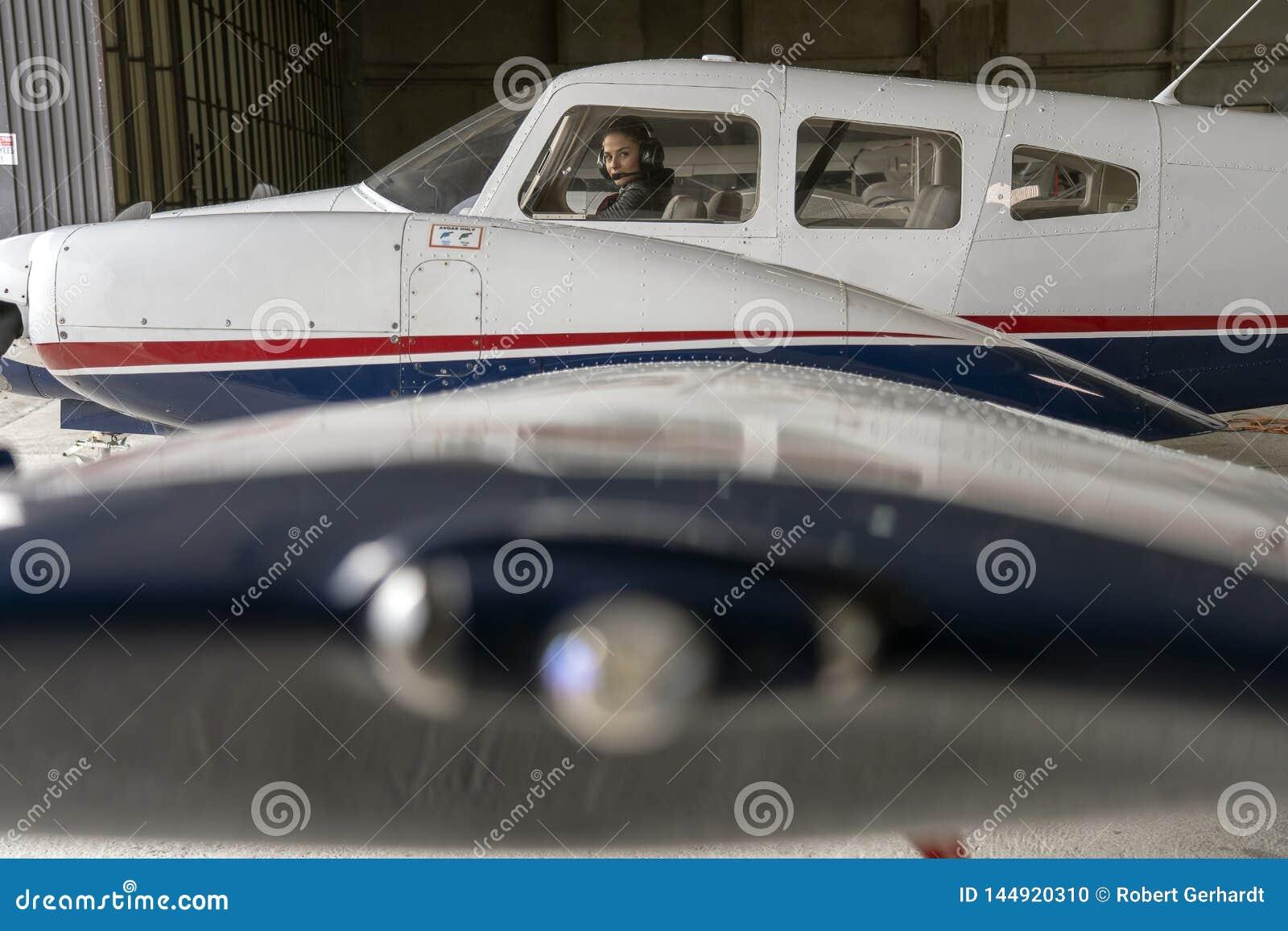 Yttre sikt av flygplan- och kvinnapiloten With Headset i cockpiten