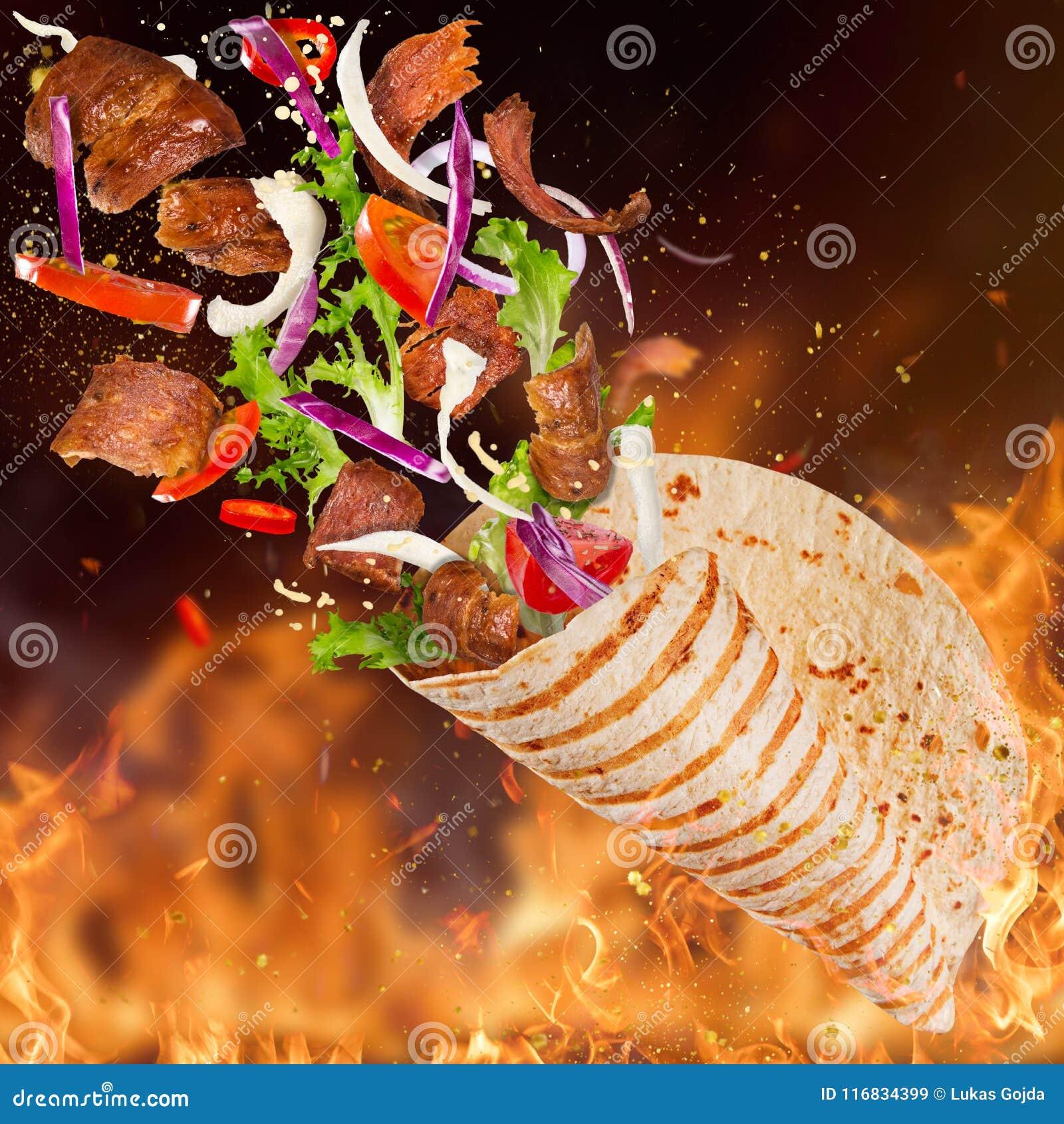 Yufka turco del kebab con los ingredientes y las llamas del vuelo