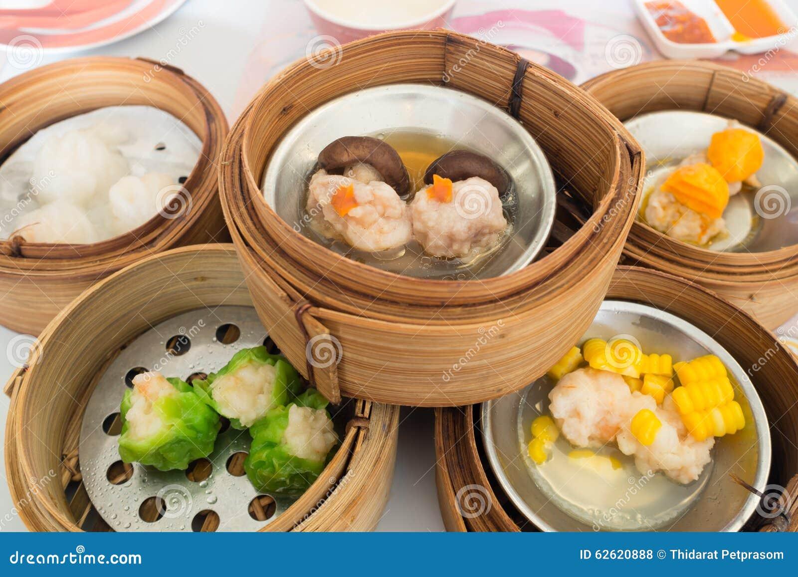 Yumcha, vário chinês cozinhou a bolinha de massa no navio de bambu no restaurante chinês Dimsum na cesta do vapor, alimento chinê