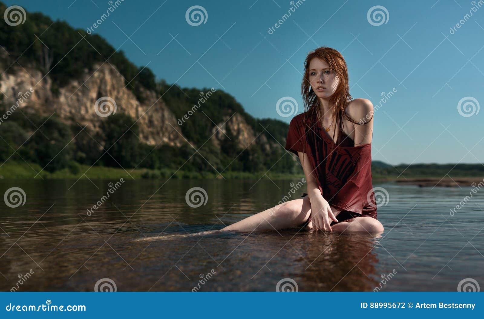 Yung härlig rödhårig manflicka i det burgundy skjortasammanträdet i floden