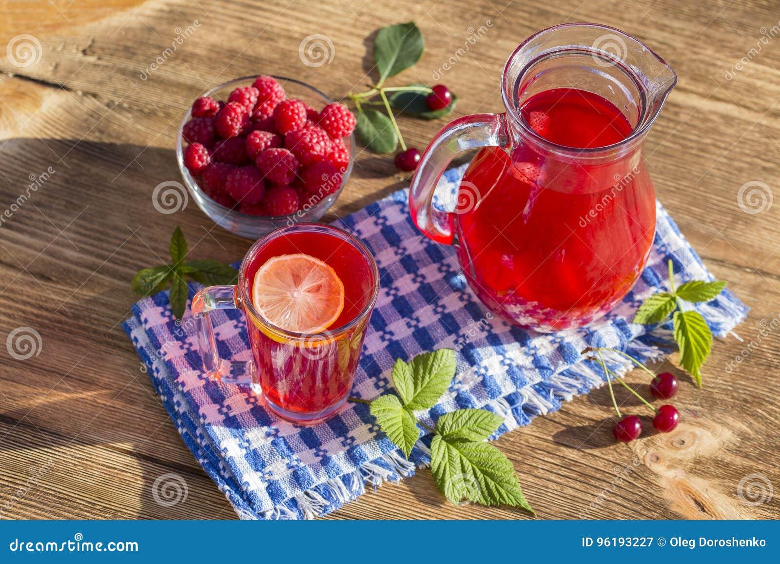 Żywienioniowy detox napój z cytryna sokiem, czerwoną truskawką, wiśnią i malinką w jasnej wodzie z lodem,