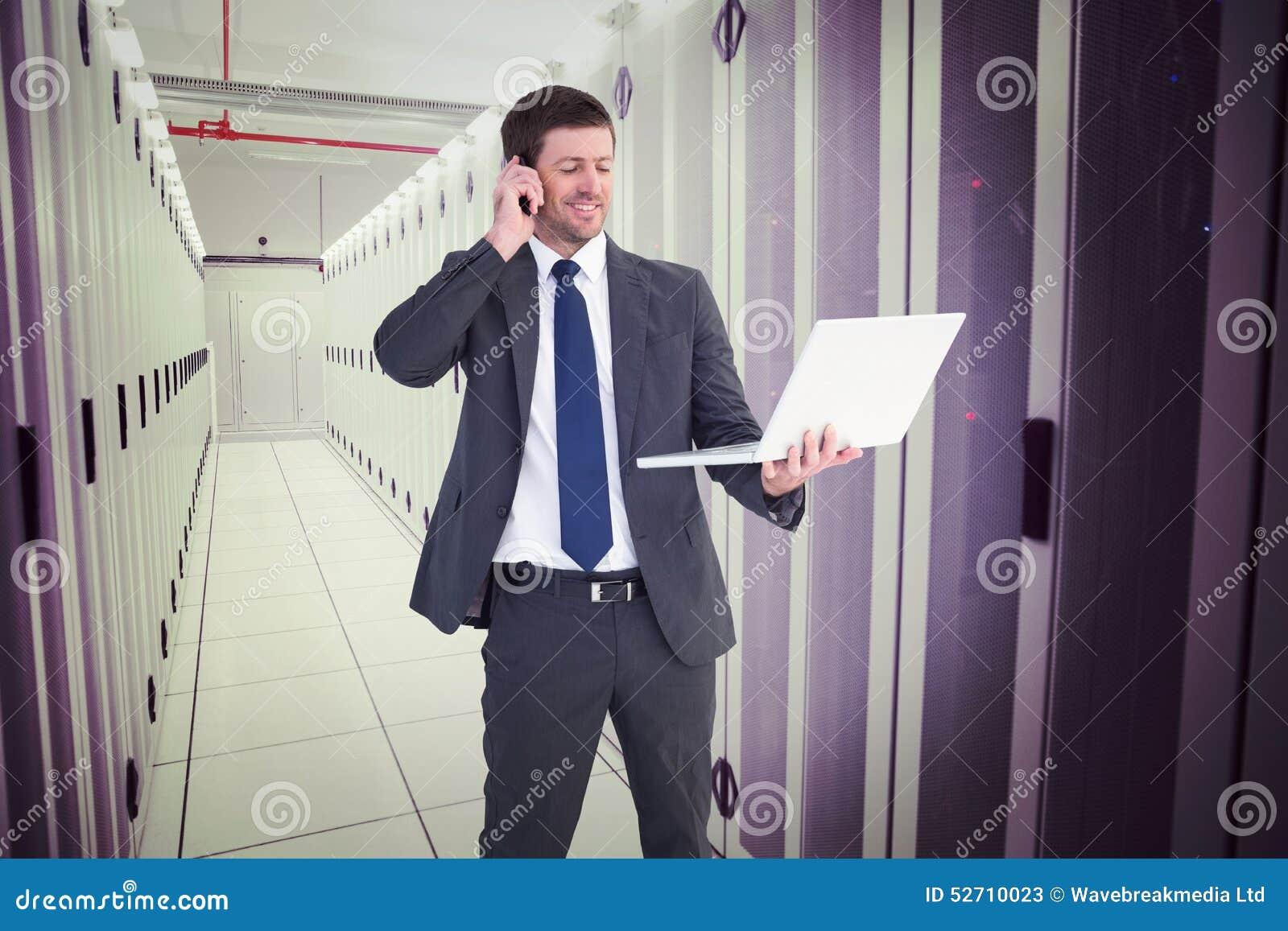 Złożony wizerunek opowiada na telefonu mienia laptopie biznesmen