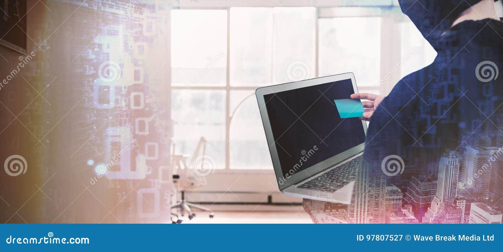 Złożony wizerunek tylni widok hacker używa laptop i kredytową kartę