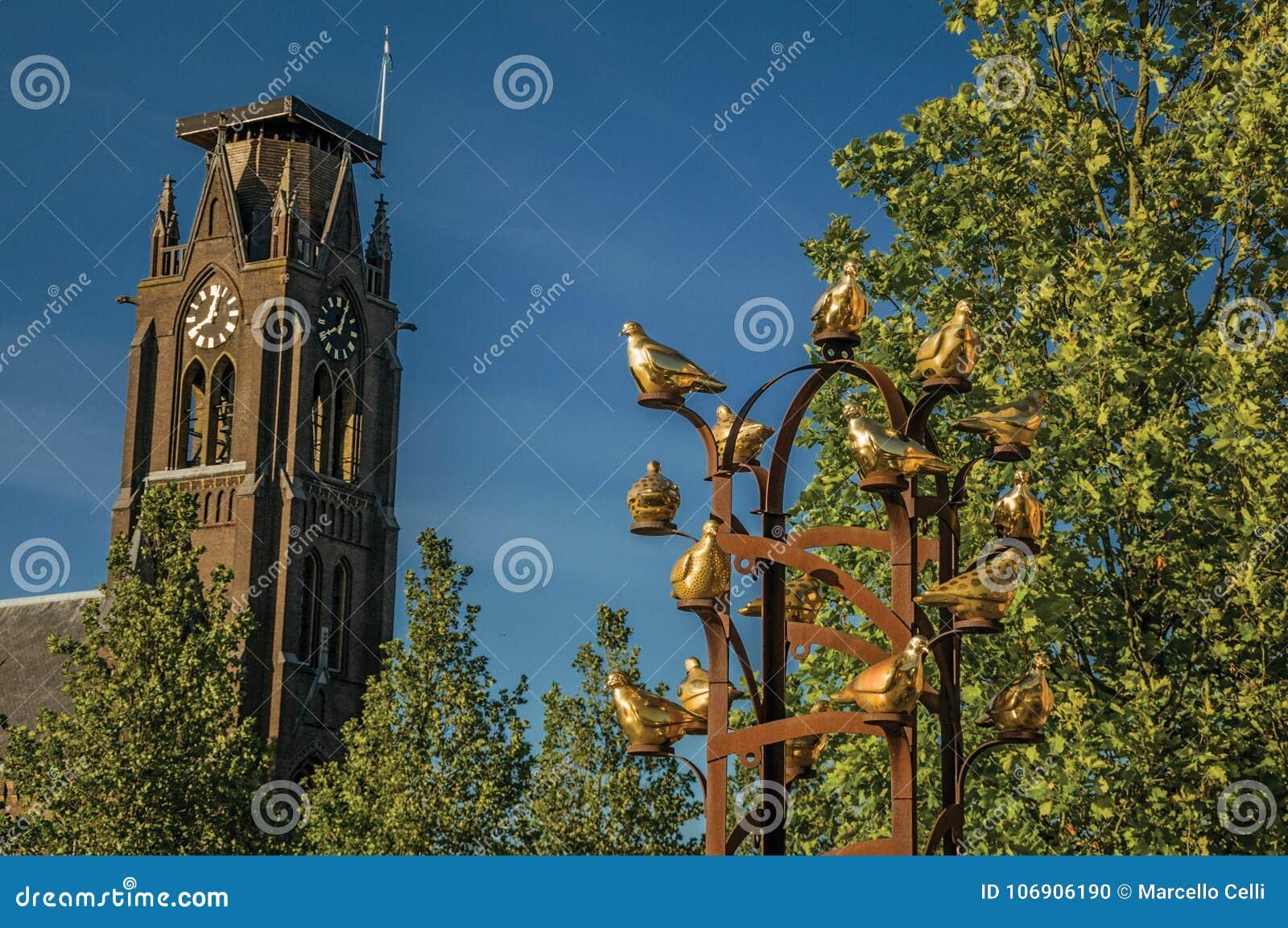 Złoci metali ptaki pomnikowi z obfitolistnym drzewem i steeple w słonecznym dniu przy Weesp